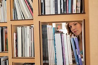 Woman choosing books from a bookshelf