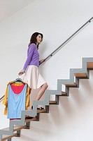 Woman moving up stairs carrying clothes (thumbnail)