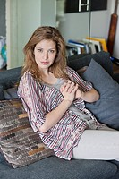 Portrait of a beautiful woman sitting on a couch (thumbnail)