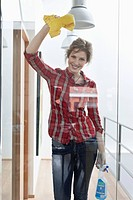 Woman cleaning a glass door and smiling (thumbnail)