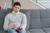 Man suffering from neckache and watching television