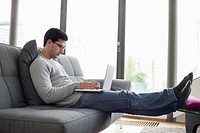 Man using a laptop on a couch