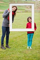Woman and her son standing with a frame in a park (thumbnail)