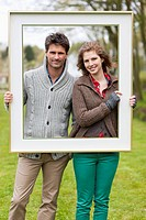 Portrait of a couple holding a frame (thumbnail)