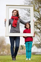 Woman and her son holding a picture frame in a park (thumbnail)