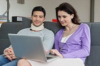 Woman using a laptop with her husband beside her (thumbnail)