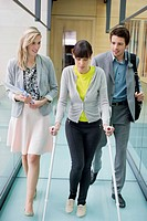 Disable woman walking with business executives in an office corridor (thumbnail)