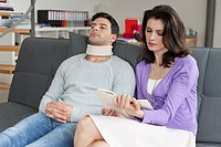 Woman reading a book for her husband suffering from neckache