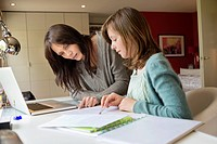 Girl studying with her mother at home (thumbnail)