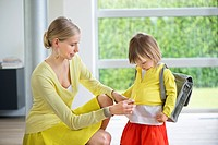 Woman preparing her daughter for school