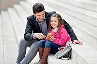 Man sitting with his daughter eating pain au chocolat (thumbnail)
