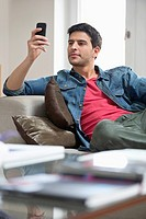 Man reclining on a couch and using a mobile phone