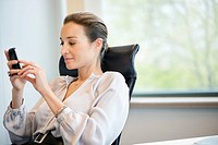 Businesswoman text messaging on a mobile phone in an office (thumbnail)