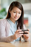 Businesswoman text messaging on a mobile phone in an office