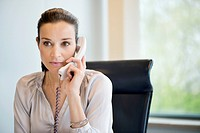 Businesswoman talking on a landline phone in an office (thumbnail)