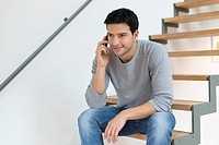 Man sitting on stairs and talking on a mobile phone
