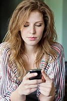 Close_up of a beautiful woman text messaging on a mobile phone