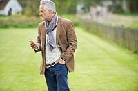 Man text messaging on a mobile phone in a lawn