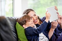 Woman with her son looking at a digital tablet and smiling