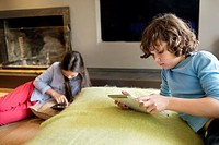 Boy and a girl using electronic gadgets at home