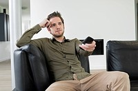 Man using remote control while watching television