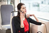 Woman traveling in a bus and talking on a mobile phone