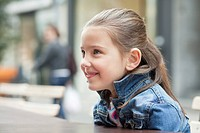 Close_up of a girl sitting at a sidewalk cafe