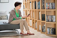 Woman sitting on a couch and reading a book (thumbnail)