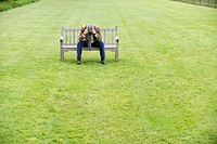 Depressed man sitting on a bench in a park