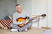 Man playing a guitar at home