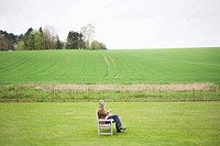 Man sitting on the bench and using a mobile phone in a field
