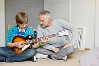 Teenage boy learning guitar with his father at home