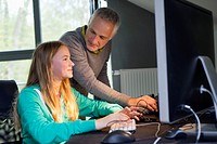 Girl using a computer with her father at home