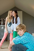 Portrait of a teenage boy with his two sisters whispering in background (thumbnail)