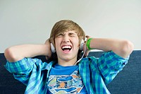 Teenage boy listening to music and looking excited