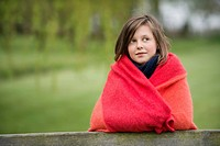 Girl wrapped in a blanket and thinking in a farm