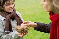 Boy showing a bird's nest to his mother