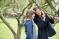 Woman with her daughter looking at a tree branch in an orchard
