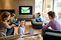 Family using electronic gadgets in a living room (thumbnail)