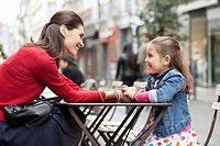 Woman and her daughter sitting at sidewalk cafe
