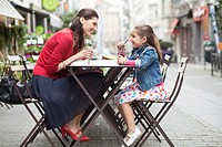 Woman and her daughter drinking at a sidewalk cafe