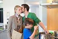 Man kissing his wife returning from shopping and son cooking in the kitchen