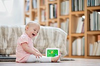 Baby girl playing with a musical block toy (thumbnail)