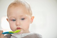Close_up of a baby girl holding a spoon