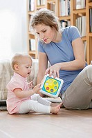 Woman sitting near her daughter playing with a toy
