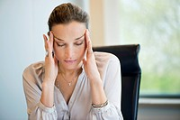 Close_up of a businesswoman suffering from a headache in an office