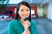 Portrait of a businesswoman holding microphone in an office