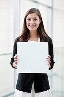 Portrait of a businesswoman holding a blank placard and smiling in an office