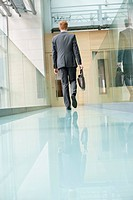 Rear view of a businessman walking in an office corridor (thumbnail)