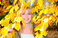 young woman looks through autumn leaves